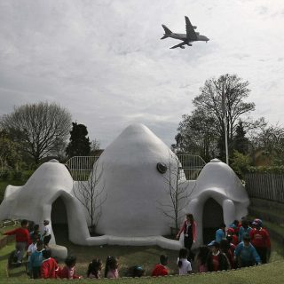 Students from Hounslow Heath infants school play around one of four adobe huts designed to help minimise the noise of aircraft landing at Heathrow airport in Hounslow, west London April 24, 2013. The playground is directly under the flight path of Heathrow's southern runway and outside play for the children is interrupted every two minutes or so by landing aircraft passing over their heads.  REUTERS/Stefan Wermuth  (BRITAIN - Tags: SOCIETY EDUCATION TPX IMAGES OF THE DAY)