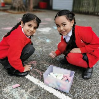 two girls chalking in playground Sept 2020
